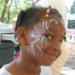 Young girl with braids and swirly face paint in pink, blue and white.