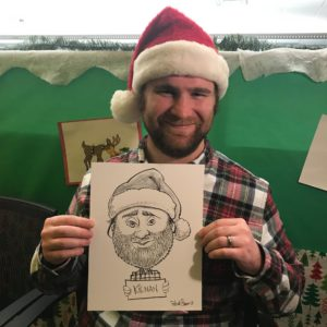 Man in santa hat at holiday party shows his caricature.