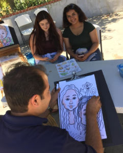 Two women have a caricature drawn by a Goofy Faces artist.
