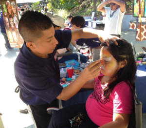 Girl gets her face painted by a Goofy Faces artist at the LA Zoo.