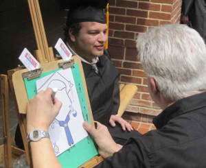 Young man in cap and gown has his caricature drawn.
