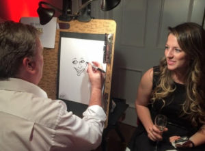 Young woman enjoys having her caricature drawn.