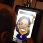 Caricature artist drawing on tablet eSketch at trade show
